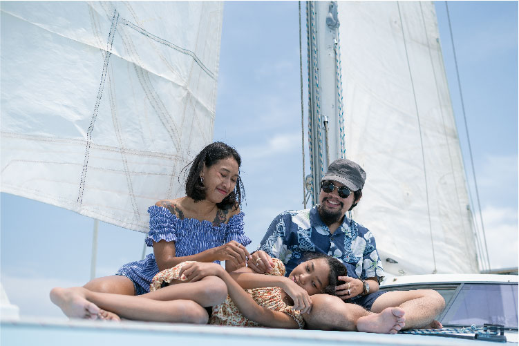 A couple and a girl on the deck of a sailboat