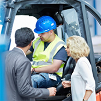 worker in forklift with man and woman looking in cabin