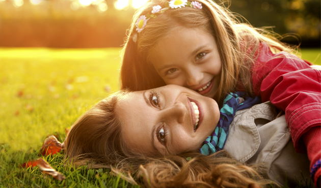 woman and girl lying in grass, smiling