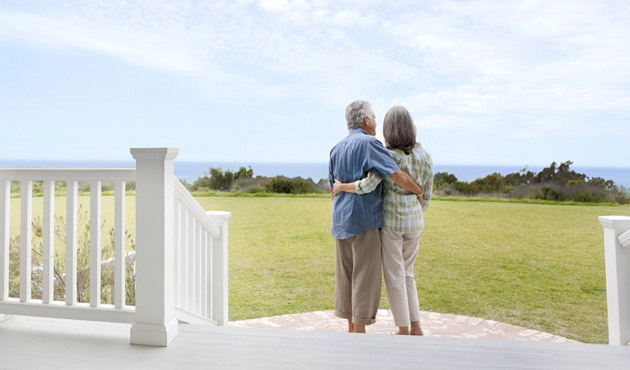 man and woman standing on porch looking at body of water