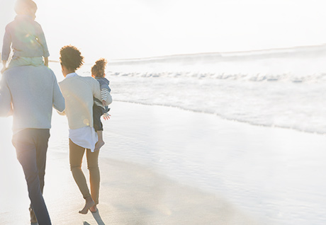man, woman and two kids walking on beach, surf and sky in background